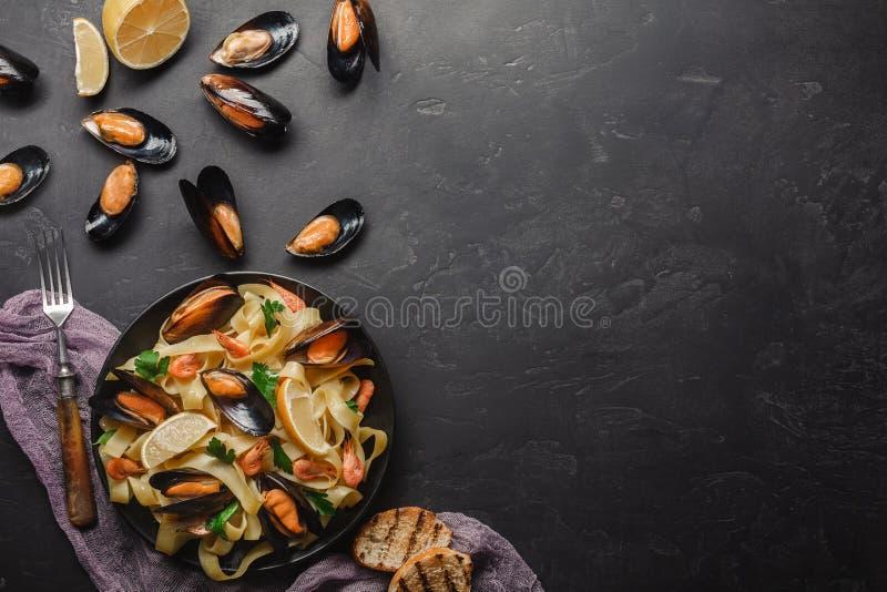 意粉vongole、意大利海鲜面团与蛤蜊和淡菜,在板材用草本和杯白酒在土气石头 免版税图库摄影