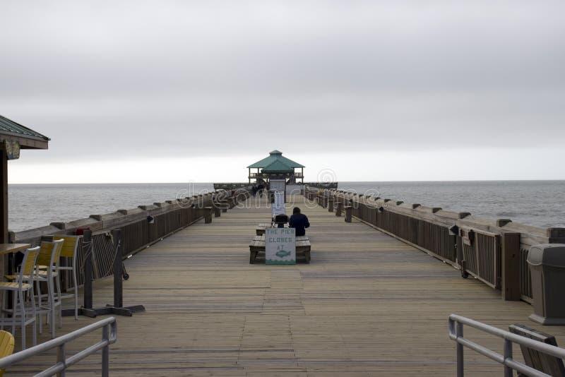 愚蠢海滩南卡罗来纳, 2018年2月17日-妇女单独坐木板走道长凳在阴暗天 图库摄影