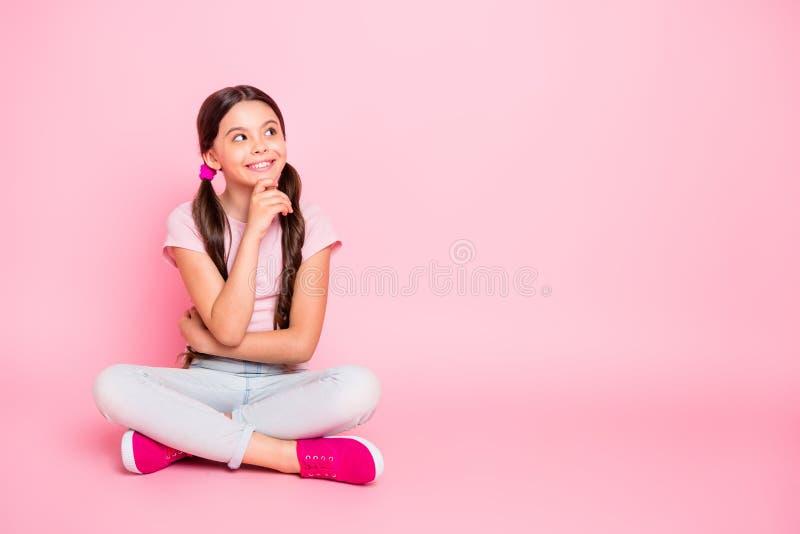感兴趣的重视的孩子神色接触下巴画象有坐的手指的穿在桃红色背景的白色T恤 免版税图库摄影