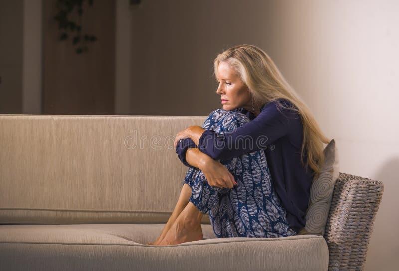 感到可爱和哀伤的妇女生活方式剧烈的画象挫败和急切坐沮丧的沙发长沙发在家遭受 免版税库存照片