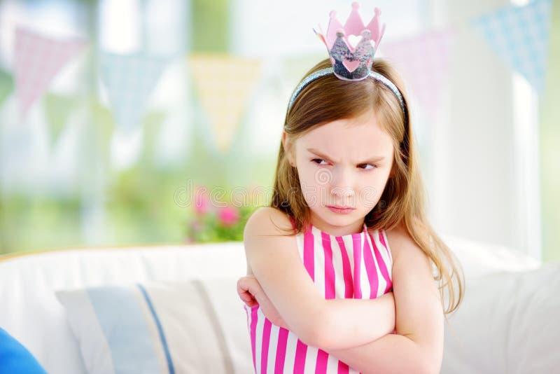感到喜怒无常的小女孩佩带的公主的冠状头饰恼怒和不满意 库存图片