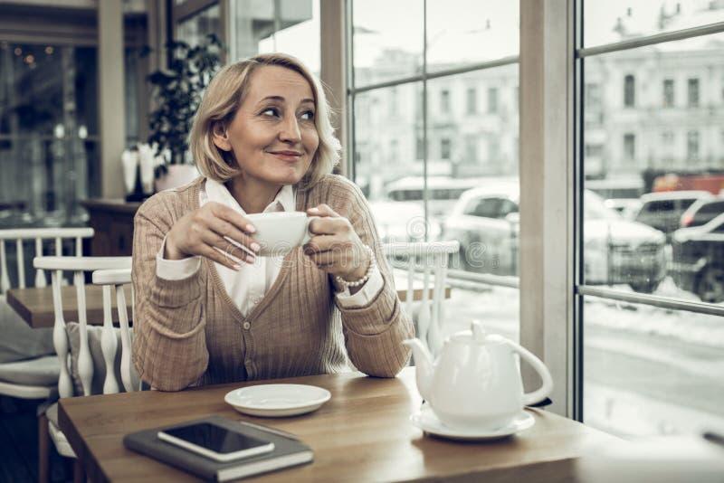 感到宜人的成熟的妇女好,当喝茶在自助食堂时 库存图片