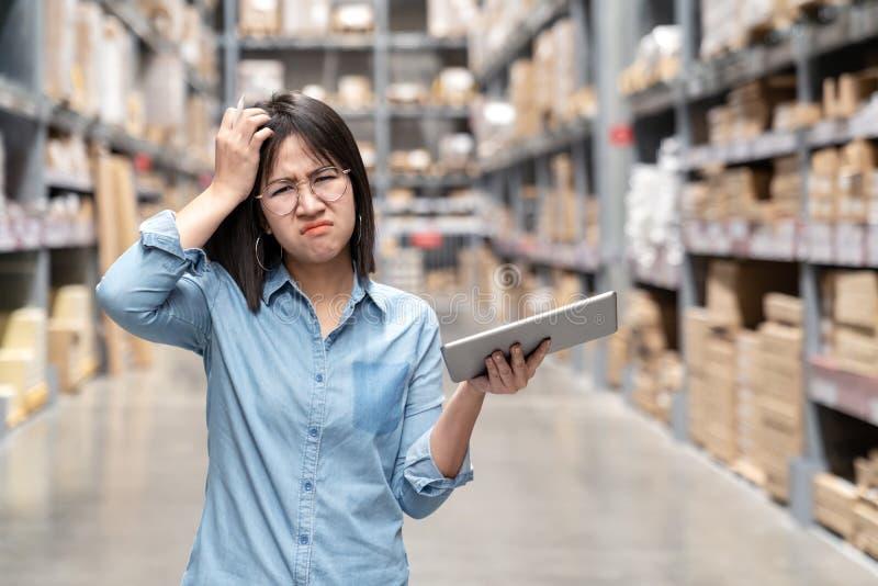 感到年轻不快乐的亚裔妇女、的审计员或者的雇员看和迷茫在仓库商店 画象少女抓 库存照片