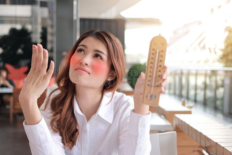 感到年轻亚裔的妇女画象拿着温度计和很热与在书桌上的高温反对阳光作用bac 免版税图库摄影
