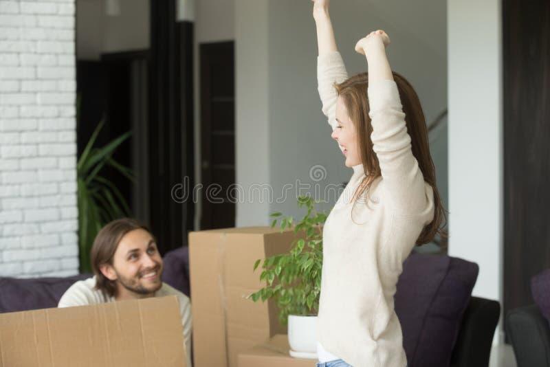 感到年轻的夫妇愉快庆祝移动新拥有在家 免版税库存图片