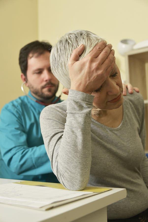 感到年长的夫人不适,有考试在医生` s办公室 库存图片
