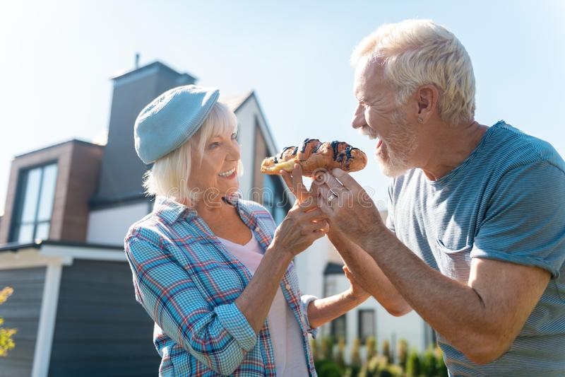 感到放光的退休的夫妇愉快,当吃新月形面包外面时 图库摄影