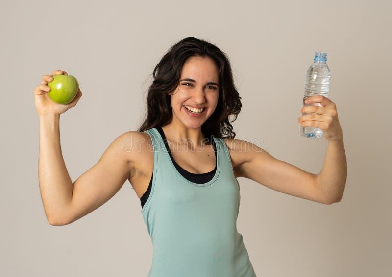 感到有吸引力的拉丁健身模型画象用苹果和的水健康和适合 库存图片