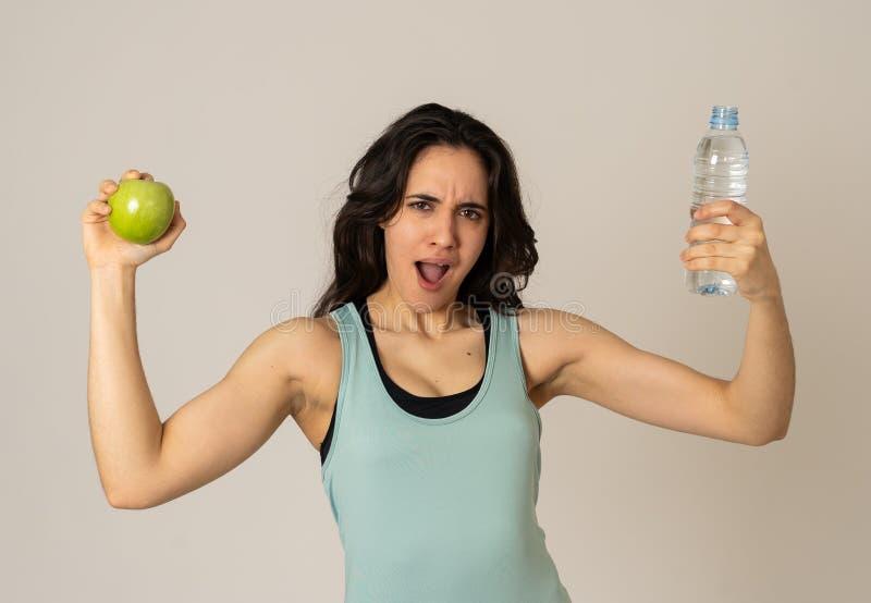 感到有吸引力的拉丁健身模型画象用苹果和的水健康和适合 库存照片
