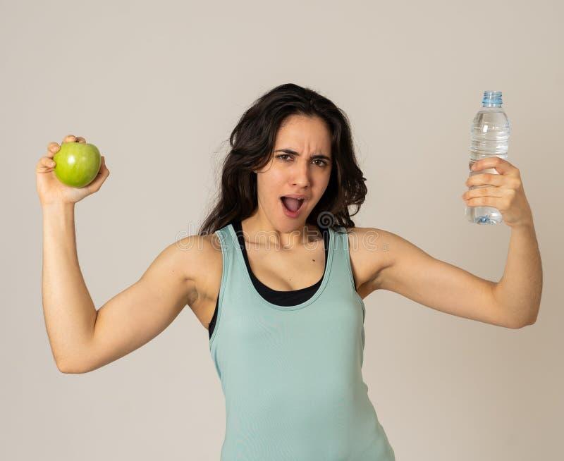 感到有吸引力的拉丁健身模型画象用苹果和的水健康和适合 免版税库存图片