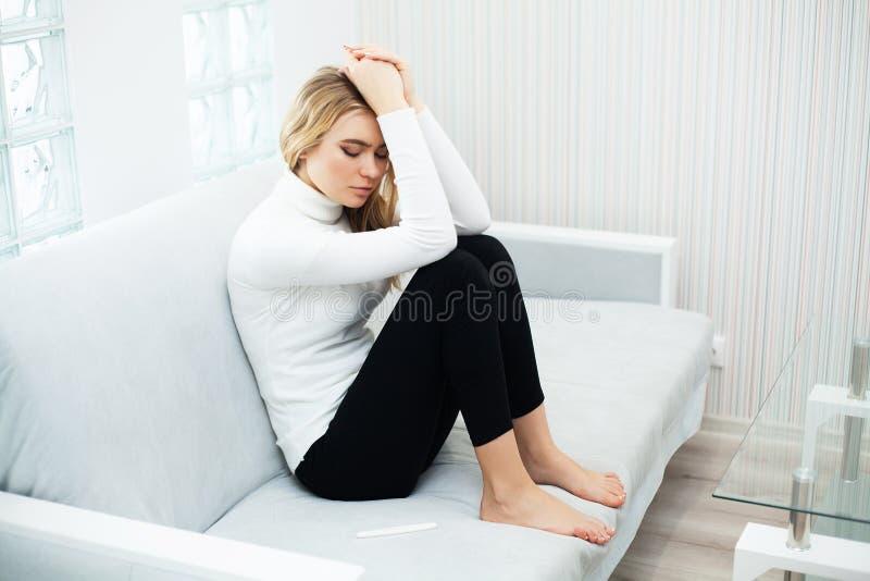 感到正面妊娠试验的年轻女人沮丧和哀伤在家看怀孕考试成绩以后 库存图片
