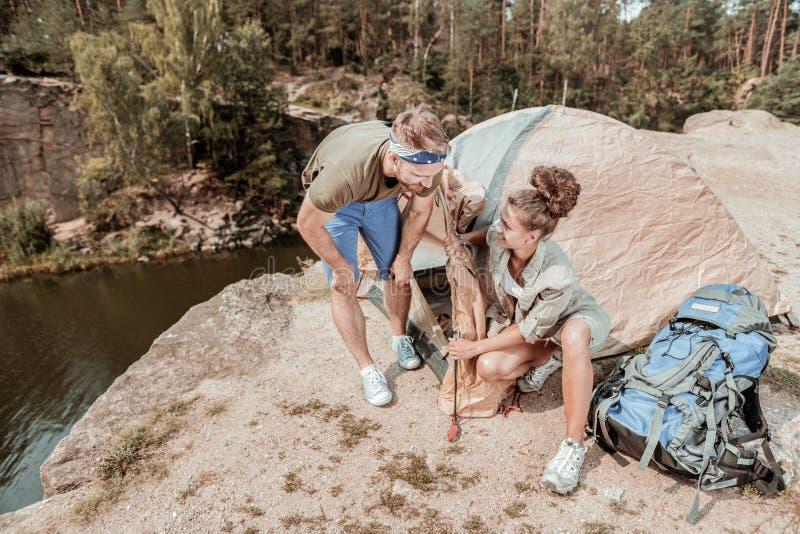 感到活跃女性的远足者愉快帮助她投入帐篷的英俊的丈夫 免版税图库摄影