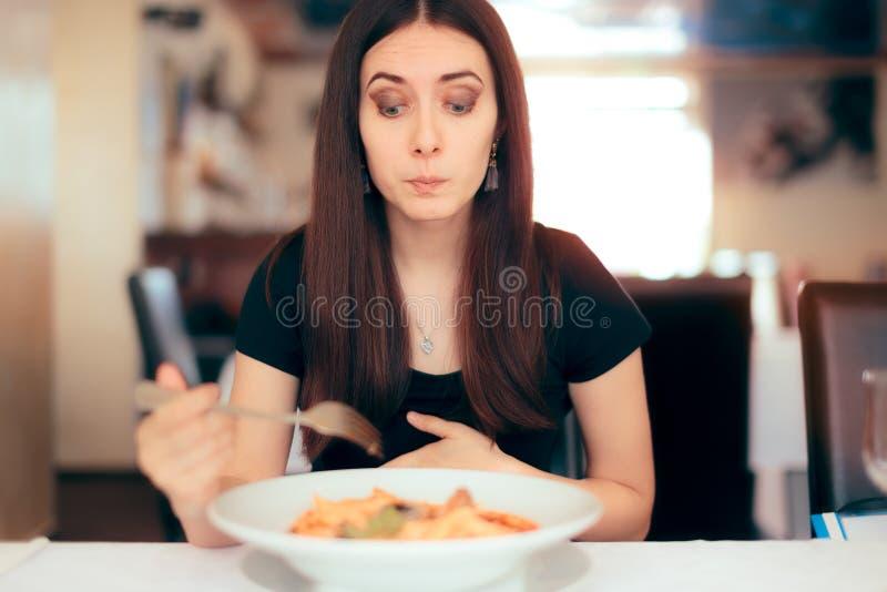 感到的妇女恶心,当吃坏食物在餐馆时 库存照片