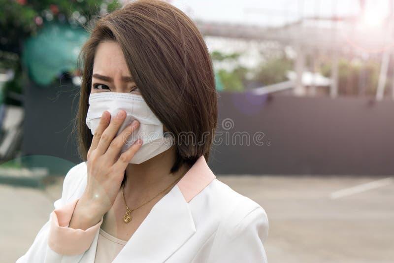 感到的防毒面具的亚裔妇女坏在街道上在有大气污染的城市 黑短发遭受病残和我们 免版税库存照片