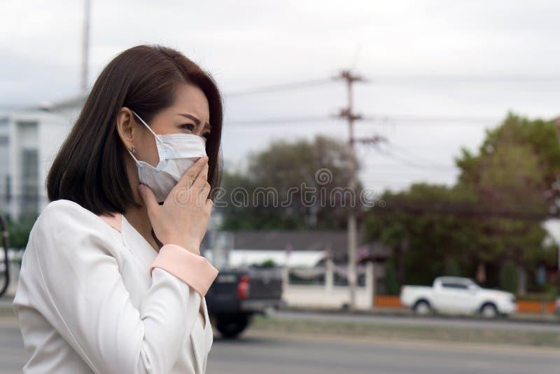 感到的防毒面具的亚裔妇女坏在街道上在有大气污染的城市 黑短发遭受病残和我们 库存照片