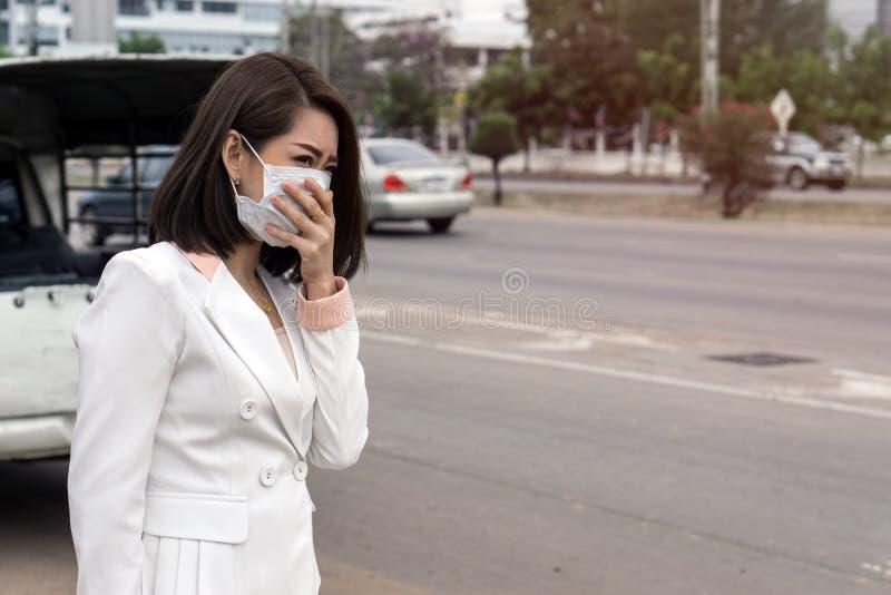 感到的防毒面具的亚裔妇女坏在街道上在有大气污染的城市 黑短发遭受病残和我们 免版税库存图片