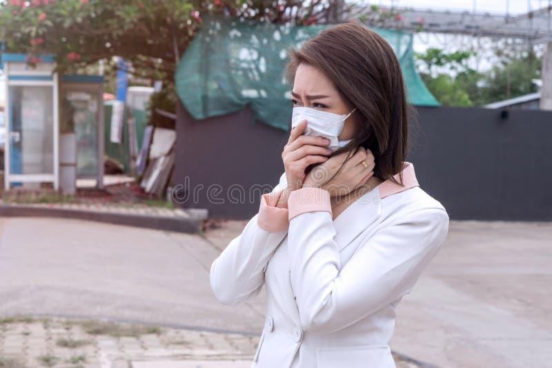 感到的防毒面具的亚裔妇女坏在街道上在有大气污染的城市 黑短发遭受病残和我们 库存图片