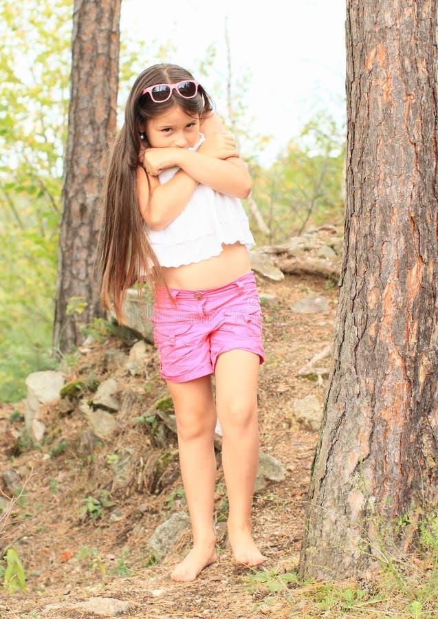 感到羞耻的女孩在森林里 免版税库存图片