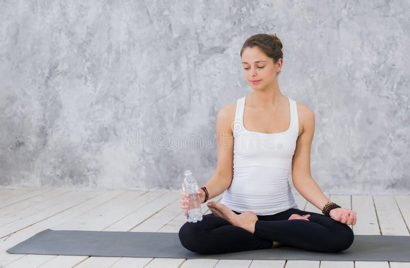 感到渴 体育衣物饮用水的疲乏的少妇,当坐锻炼席子时 免版税库存图片