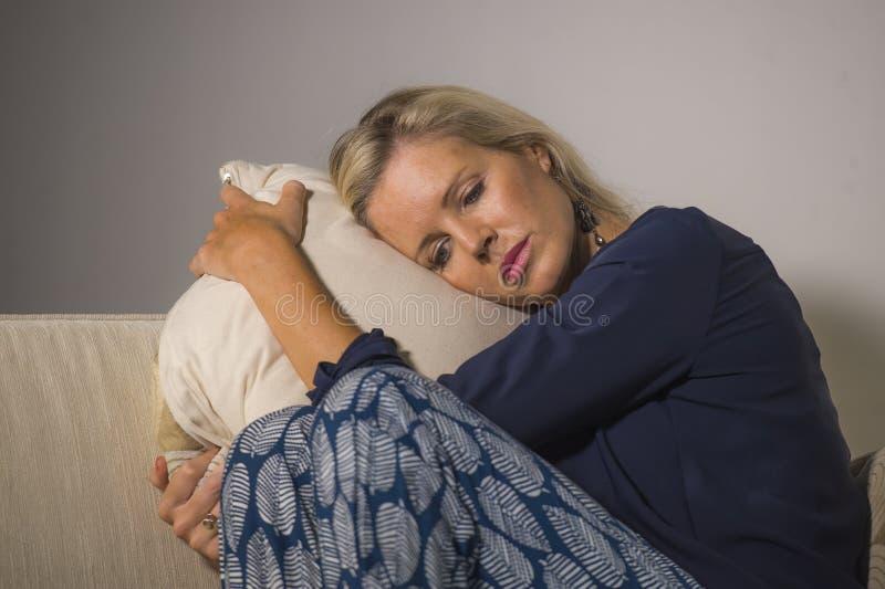 感到40s沮丧的和急切美丽的白肤金发的妇女遭受的消沉挫败和偏僻在家坐沙发长沙发tho 免版税图库摄影