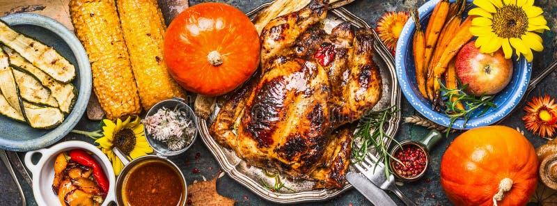 感恩天食物 各种各样的烤菜、烤鸡或者火鸡和南瓜与向日葵装饰在黑暗的backgr