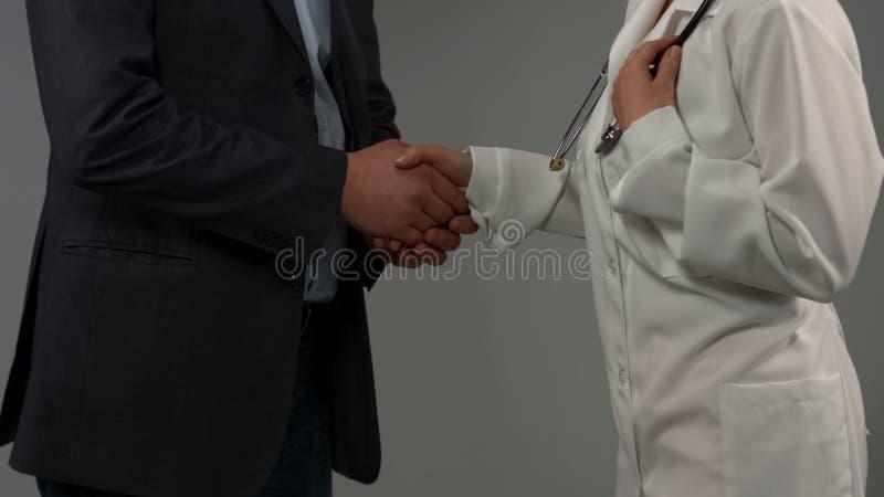 感恩的握手,成功的治疗,医疗保健的患者和医生 免版税库存照片