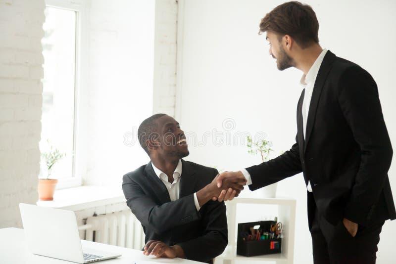 感恩的白种人行政握手非洲雇员congra 库存图片