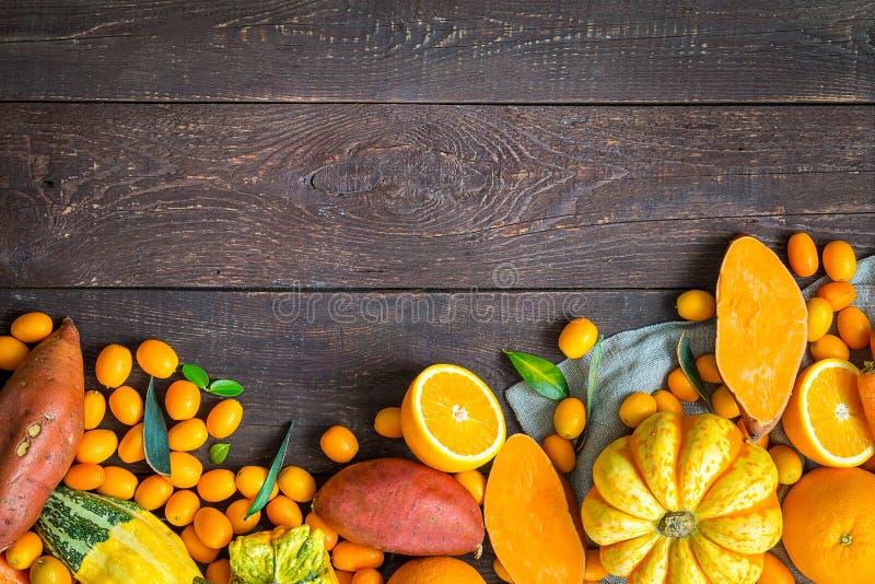 感恩秋天橙色背景、在黑暗的木背景的品种水果和蔬菜与文本的自由空间 免版税库存照片