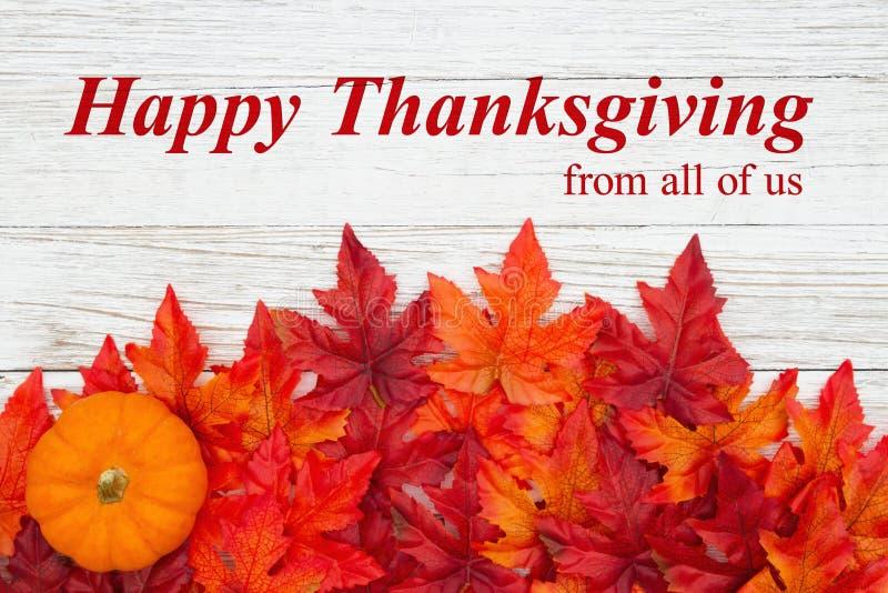 感恩节快乐,用红橙秋叶和南瓜在风化的木头上问候 库存图片