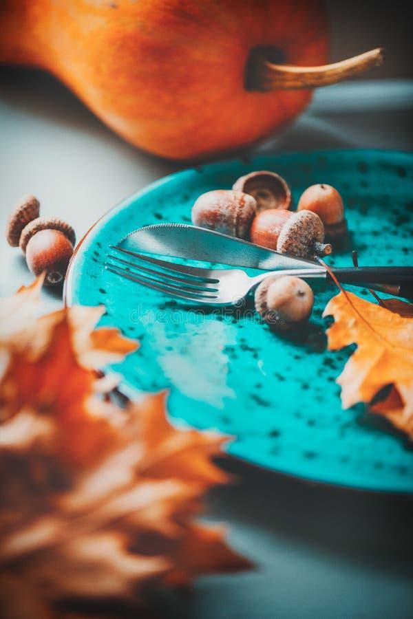 感恩节晚餐 感恩木桌服务,用明亮的橡木叶子和橡子装饰 免版税库存照片