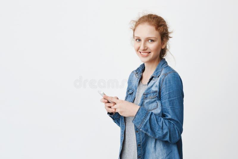 感情年轻红头发人女孩演播室射击有逗人喜爱的微笑的,站立半转动与梳的头发,拿着智能手机 库存图片