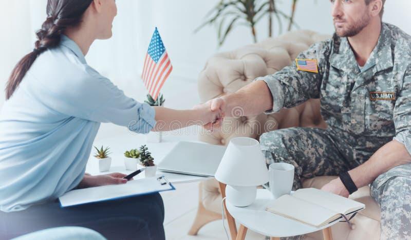 感激的军事仆人与女性治疗师握手 免版税库存照片