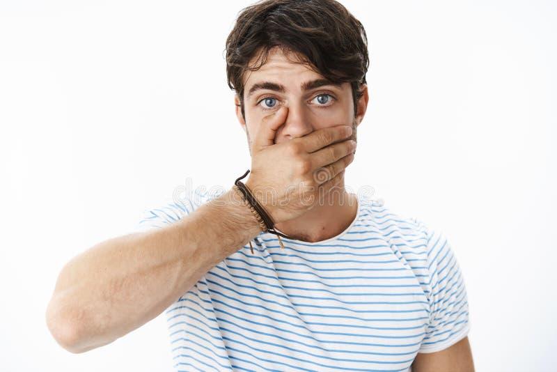 感觉与棕榈的强烈和担心的盖的嘴作为体会的震惊和有关帅哥说愚笨 库存图片