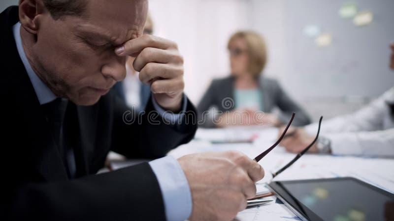 感觉剧烈的头痛的企业工作者在会议、工作失望和重音上 免版税库存图片