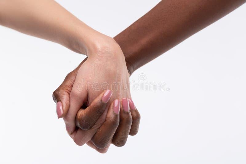 感觉尽管肤色的强有力的妇女相等的握手的 免版税库存照片