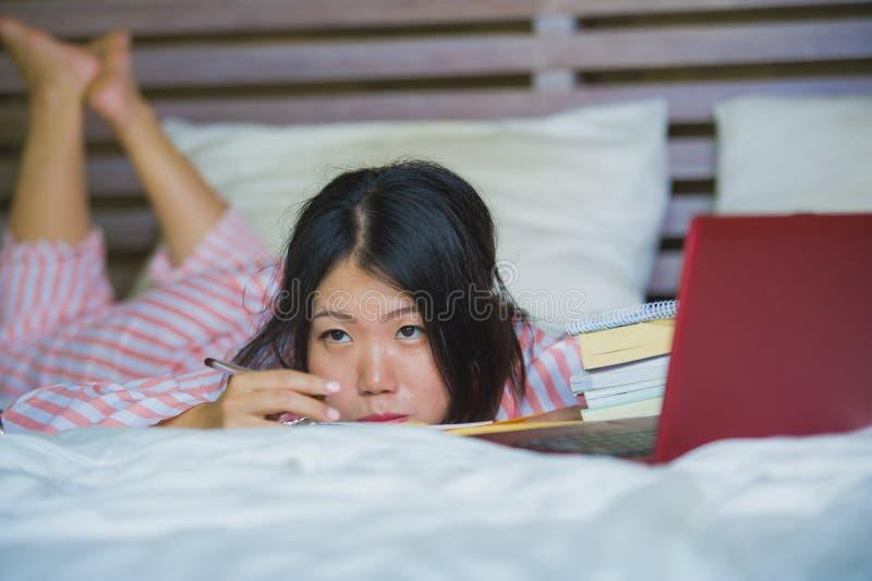 感觉年轻沮丧和疲乏的亚裔日本大学生的妇女学习与膝上型计算机的乏味和懒惰准备的检查 库存图片