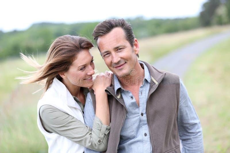 感觉愉快走的中年夫妇在乡下 免版税库存照片
