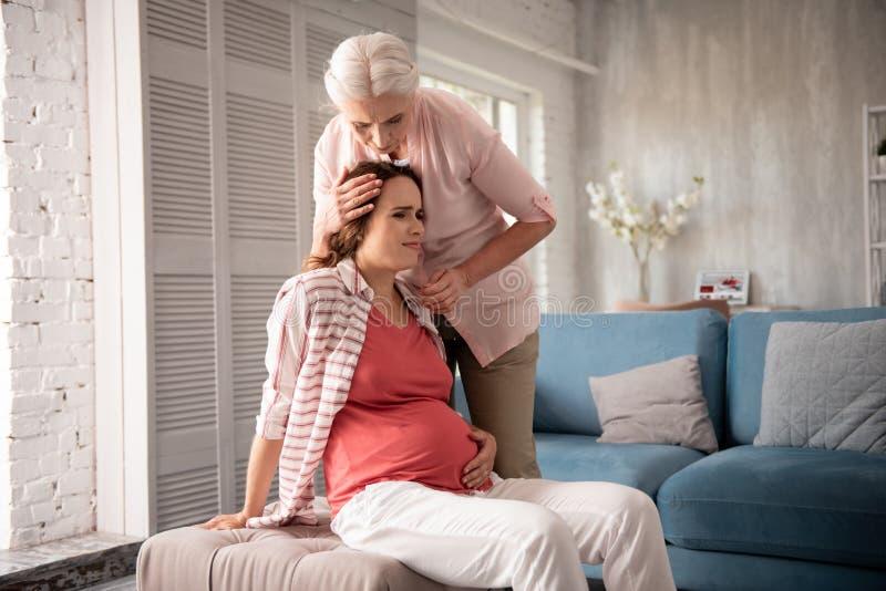 感觉有同情心的母亲担心,当感到怀孕的女儿头昏眼花时 库存图片