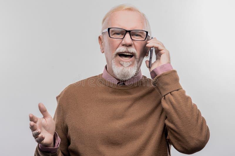 感觉有胡子的年长的人激发,当告诉他爱恋的有同情心的妻子时 库存照片