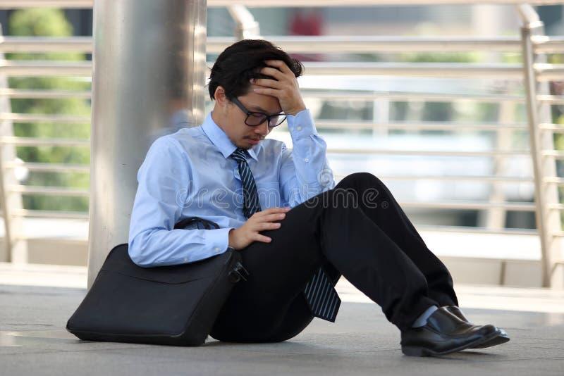 感觉沮丧的被注重的年轻亚裔的人画象坐边路办公室地板和疲倦与工作 免版税库存图片