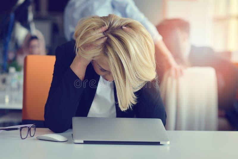 感觉疲倦和注重 保留眼睛的沮丧的妇女从疲劳关闭了,当坐在办公室时 免版税库存照片