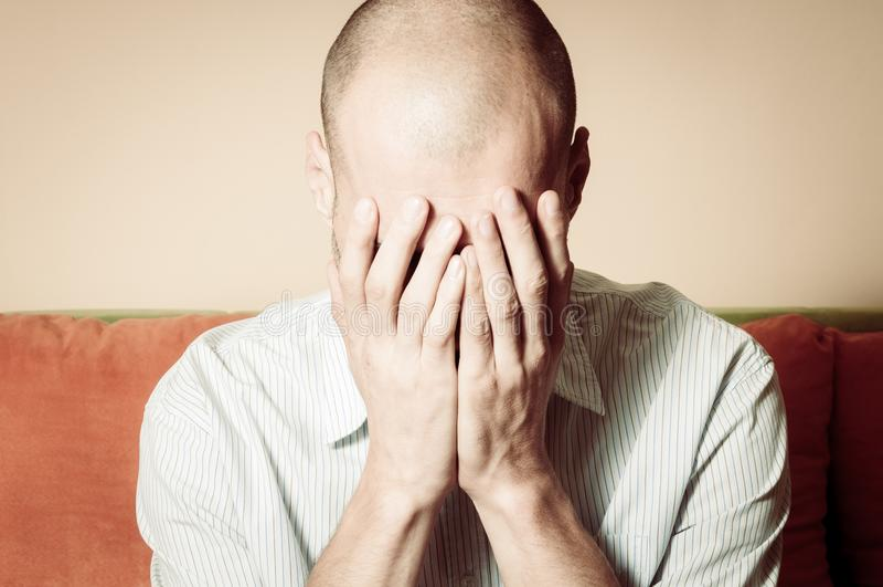 感觉的衬衣的年轻秃头人沮丧的和凄惨的盖子他的面孔用他的手和啼声在他的屋子里 免版税库存照片