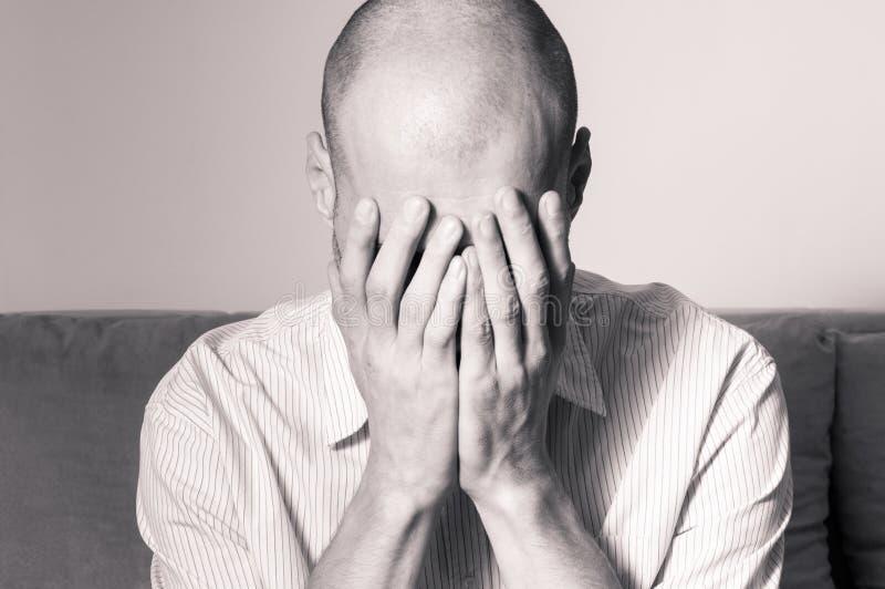 感觉的衬衣的年轻秃头人沮丧的和凄惨的盖子他的面孔用他的手和啼声在他的屋子里 免版税库存图片