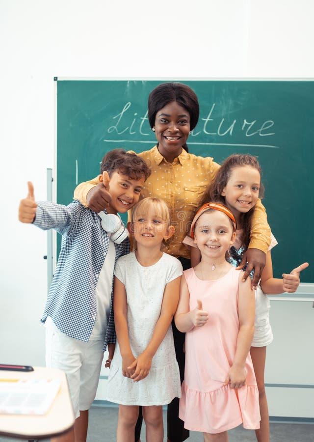 感觉真实地愉快的身分的孩子在他们亲切的爱恋的老师附近 图库摄影