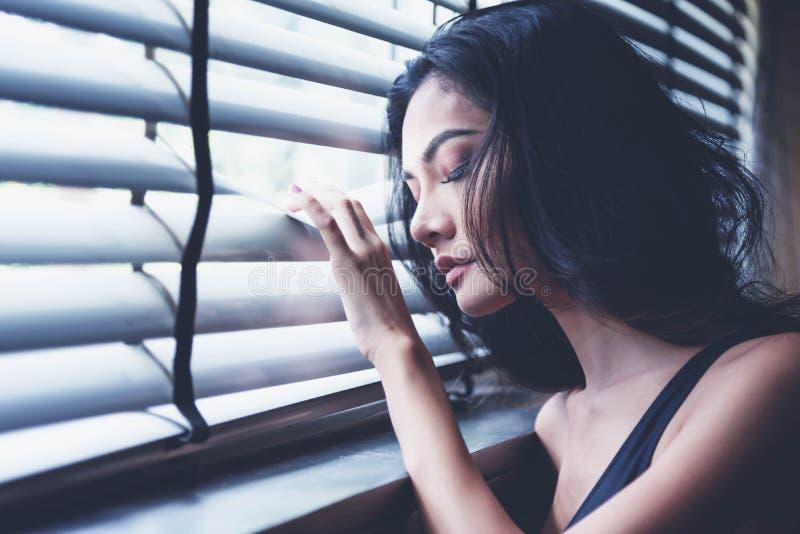感觉自由的妇女 拿着天窗窗口的妇女被监禁做自由或缺乏自由 在winndow的女孩倾斜 库存图片