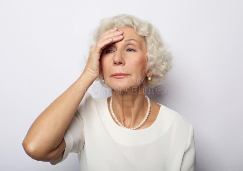 感觉蓝色担心问题的资深妇女,沉思生气哀伤的中部变老了灰发的夫人 免版税库存图片