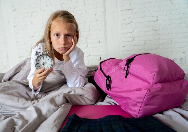 感觉逗人喜爱的女孩非常疲倦了清早不要准备好学校 免版税库存照片