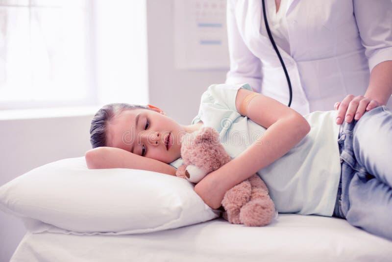 感觉非常病残的小逗人喜爱的女孩说谎在床上在有她的玩具的医院 免版税图库摄影