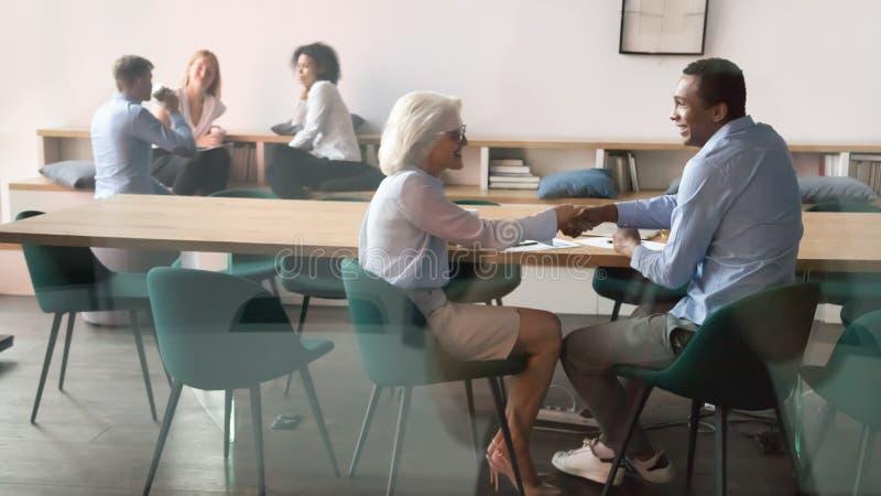 感谢年迈的经理的愉快的非洲客户握手做生意 免版税库存照片