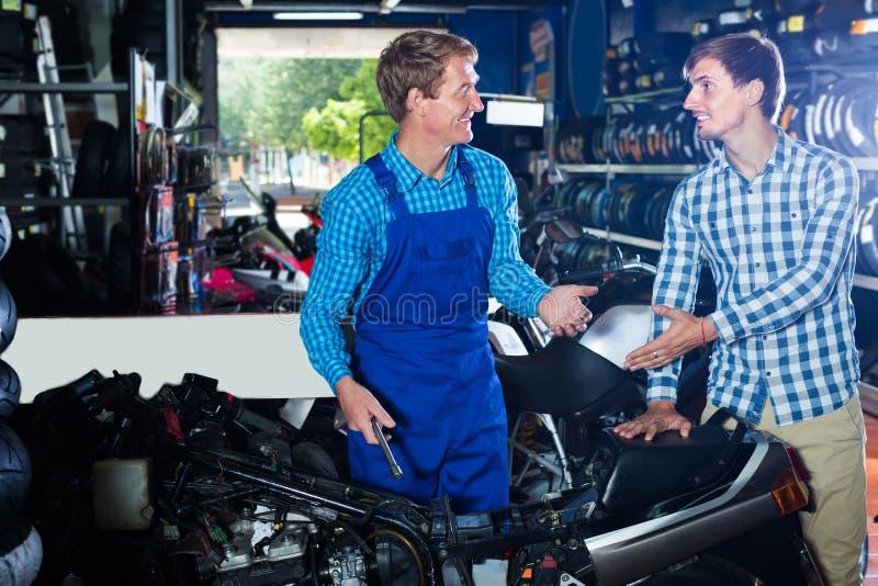 感兴趣的人顾客询问技术员关于摩托车 免版税库存图片